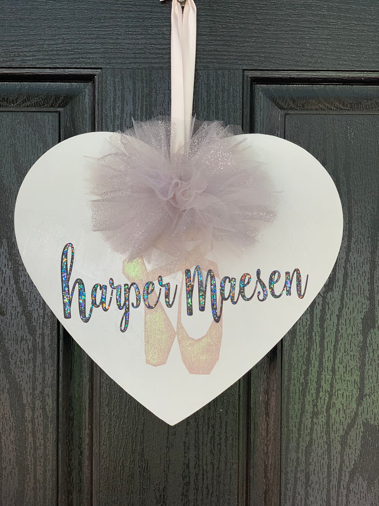 Personalized Wood Heart shows an image of a wooden heart hanging with personalized name and tulle pom pom attached with a satin ribbon.