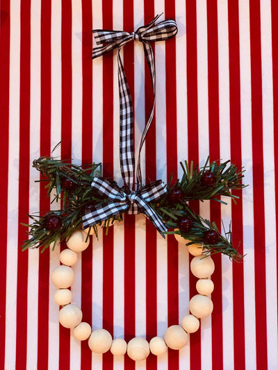 Mini Beaded Wreath Ornament is shown with a mixture of 16mm and 12mm beads with pine greenery and red berries.  It has a buffalo plaid bow and ribbon to hang.