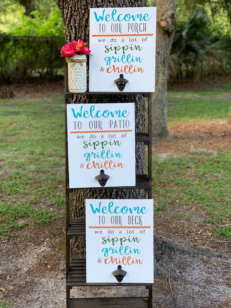 Welcome To Our (Porch/Patio/Deck) June Sign Of The Month shows the sign in an outdoor setting with three versions of the saying porch, patio and deck.  All three signs are white with multicolor lettering and the vintage bottle opener.  Each sing sold separately.