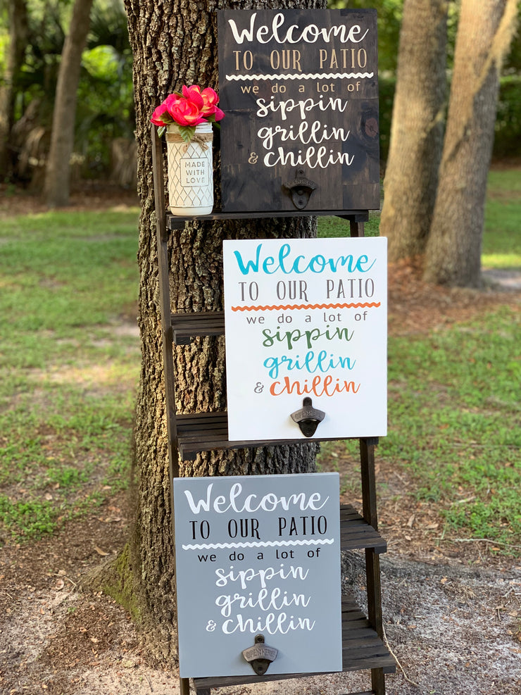 Welcome To Our (Porch/Patio/Deck) June Sign Of The Month shows the sign in an outdoor setting with three color variants.  Stained with white and tan lettering, white  multicolor and gray with white and black lettering.  All three signs have the vintage bottle opener.  Each sign sold separately.