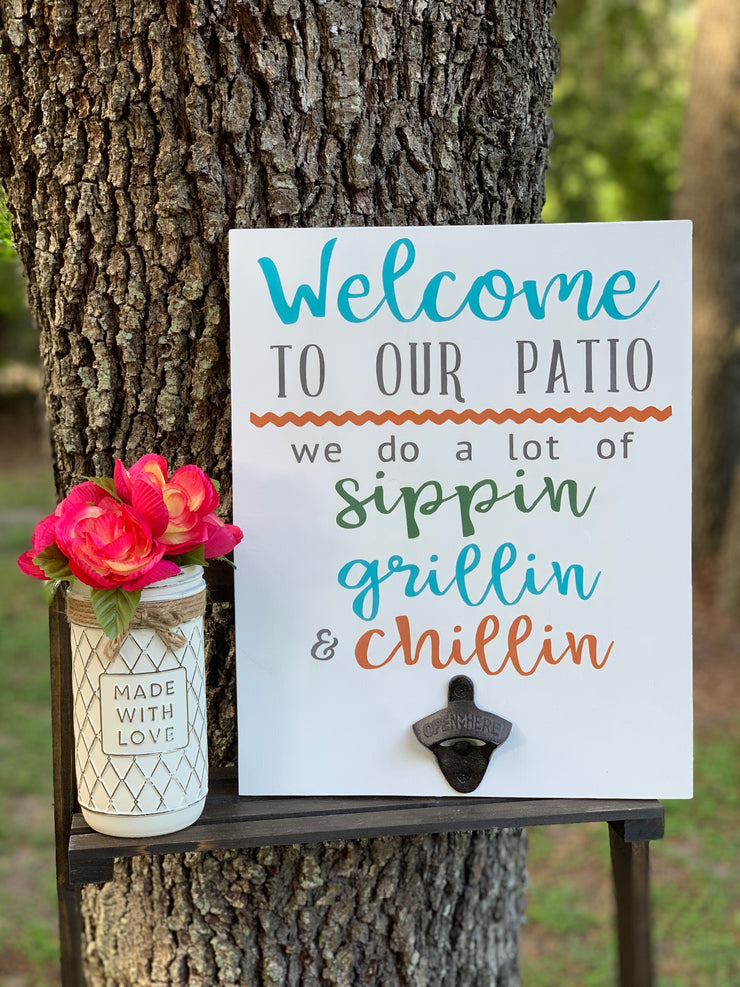 Welcome To Our (Porch/Patio/Deck) June Sign Of The Month shows an image of the sign in an outdoor setting with the white multicolor lettering and vintage bottle opener. Decor vase and flowers sold separately.