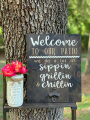 Welcome To Our (Porch/Patio/Deck) June Sign Of The Month shows an image of the sign in an outdoor setting with a stained jacobean sign with white and tan lettering and a vintage bottle opener.  Floral arrangement with vase sold separately.