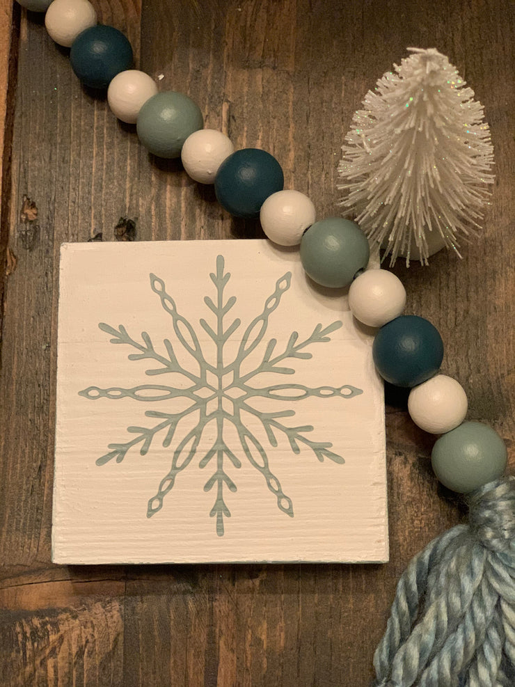 Snowflake Tiered Tray Block Sign shows the sea glass green snowflake with the wooded beaded garland.  Each item sold separately.