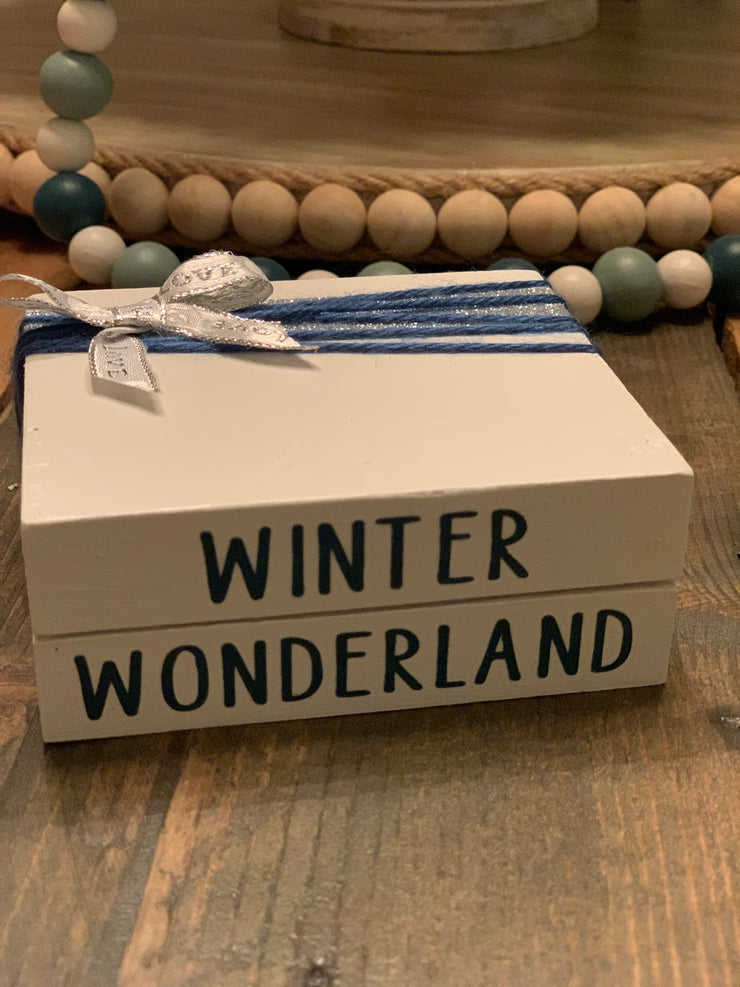 Winter Wonderland Wooden Books shows a close up of the wooden book stack. This has a silver bow and blue yarn wrap with Antebellum Blue hand painted winter wonderland.