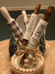 "Winter Mini Rolling Pin Sayings shows both Let it snow and snuggle together as well as the buffalo plaid 5"" and 7"" rolling pins in a glass jar.  Each rolling pin is sold separately."