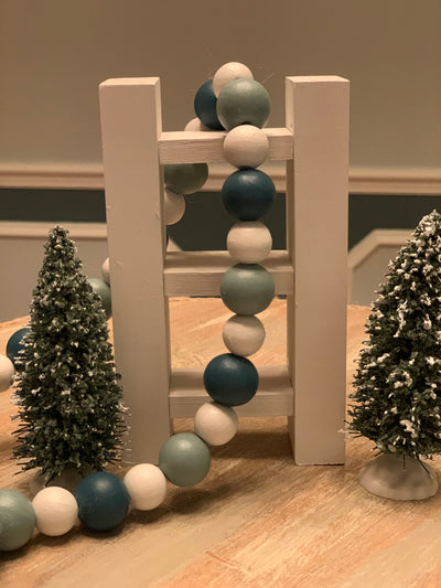 Mini Tiered Tray Wood Ladder shows an image of the white ladder with wood bead garland and pine tree decor.  Each item is sold separately.