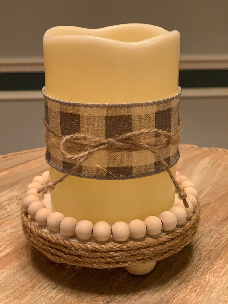 Flameless Battery Operated Wax Candle shows the gray and white check ribbon wrapped candle with a twine accent.  Wooden beaded riser sold separately.