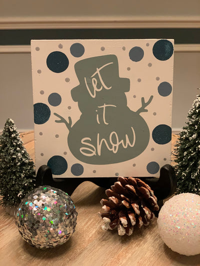 Let It Snow Snowman Sign is shown sitting in a frame holder (which does not come with the sign).  This sign can be leaned against any decor item in your tiered tray as well.  The other items shown in the picture are not sold with the sign.