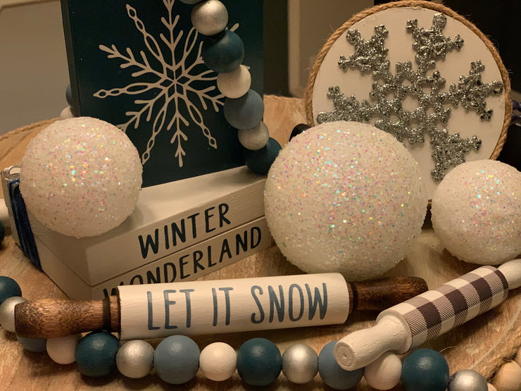"Winter Wonderland Wooden Books / Gift Set is shown with a set of wooden books, 3 white glitter snowballs, one 5"" mini buffalo plaid rolling pin, one 7"" Let It Snow mini rolling pin, one 4x4 3D double sided glitter snowflake sign, and one 3.5 x 4"" blue snowflake block sign."