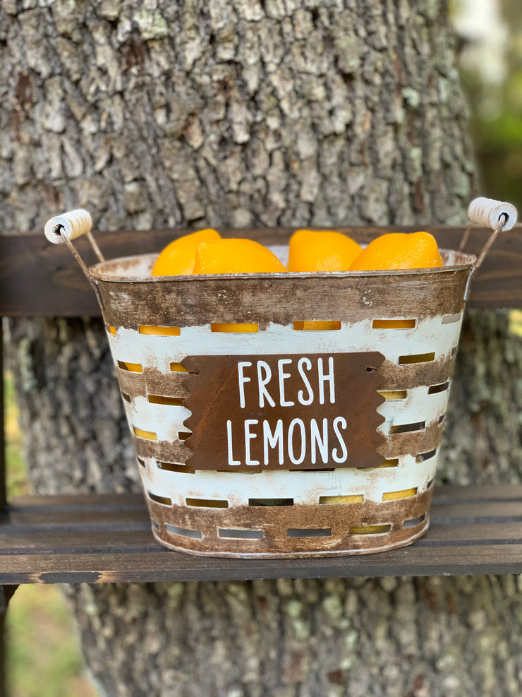 Small Olive Fresh Lemons Basket shows an image of the basket sitting on a ladder outside.  Lemons sold separately.