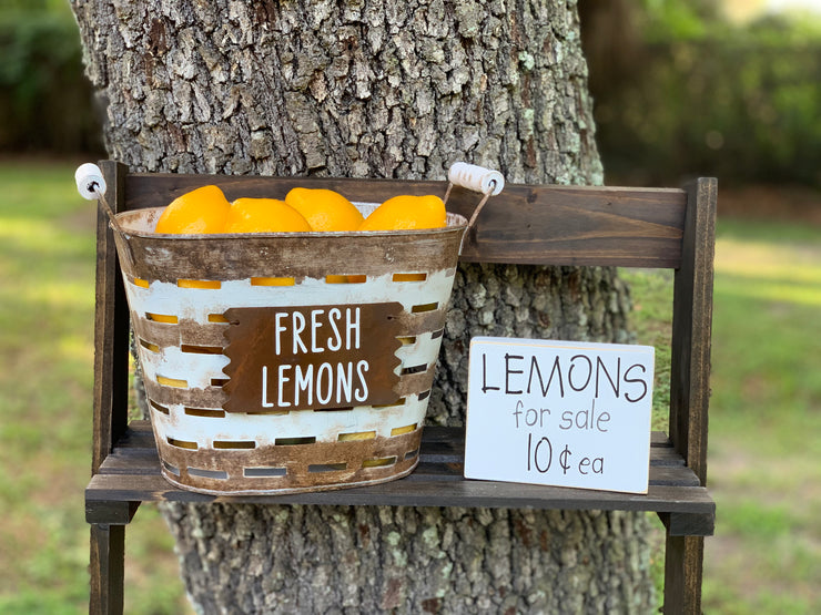 Lemons For Sale 10 Cents Each shows an alternative image of the block sign displayed with a rustic olive bucket with fresh lemons. Each item sold separately.
