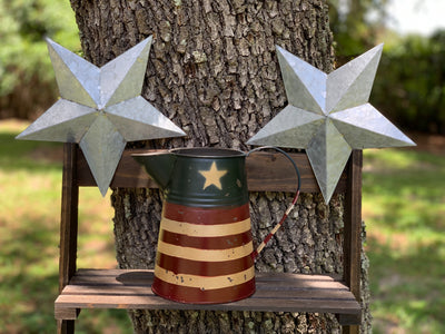 Primitive Red, Tan, and Navy Metal Pitcher is displayed outside sitting on a ladder with metal stars.  Each item sold separately.