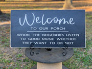Welcome To Our Porch Sign is shown sitting outside on an easel (not included with sign).  The sign shown is distressed black with ivory writing.