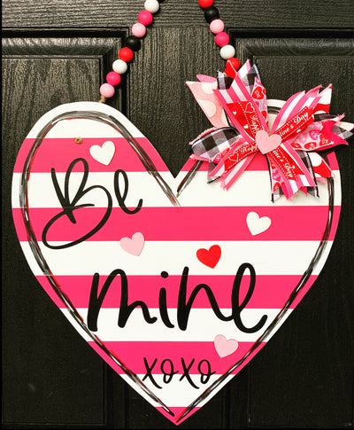 Valentine Stripe Heart Door Hanger is shown hanging on the door.  This beautiful white and pink stripe heart has real wood heart cutouts added with a multicolored wood bead garland to hang and a colorful burlap bow.