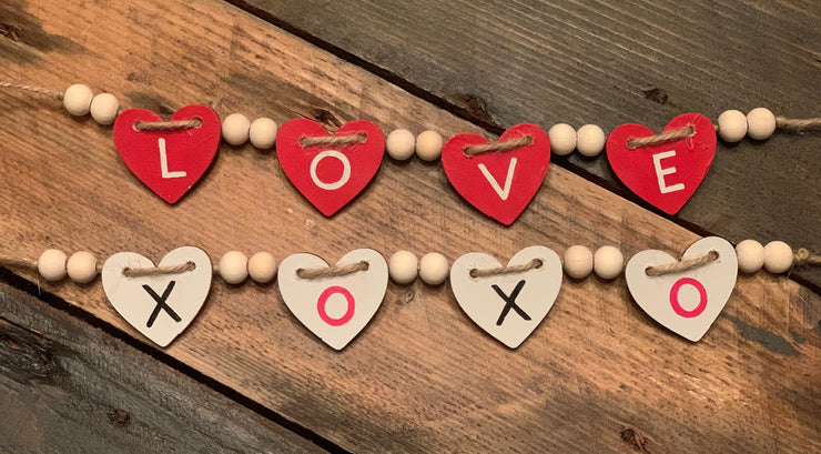 Mini Wood Heart and Bead Tiered Tray Garland (Valentine) shows the two colors side by side.  Red with love and white with xoxo