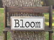 Bloom Wood Box Sign is shown sitting outside on a ladder.