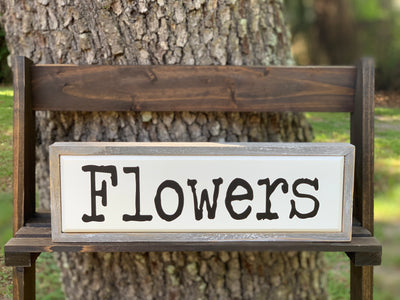Flowers Wood Box Sign is shown sitting on a ladder outside.