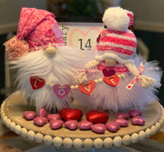 Valentine Day Gnomes are paired with a boy and girl shown.  They are wrapped with the love heart tiered tray garland sitting on top of a tiered tray.  Each gnome is sold separately unless bought together as a pair.