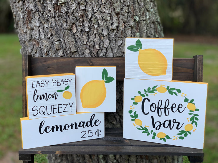 Lemonade 25 Cents shows an image of a group of lemon block signs sitting on a ladder outside.  Each sign sold separately.