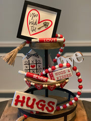 "This is the Red Gift Box Set. This set comes with a 6x6"" wood frame that says you hold the key, one mini wood xoxo house, a hugs and kisses wooden book set, one 5"" and 7"" rolling pins, one 45"" red and white wood bead garland, one heart LOVE wood garland, one HUGS 3D wood sign, and one LOVE script wood cutout."