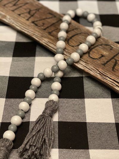 Gray and White Wood Bead Garland is shown draped over a wood sign.  Wood sign is not for sale.