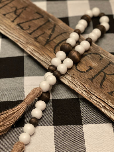 White and Jacobean Bean Garland (3 sized beads) is shown draped across a wood sign.  Wood sign is not for sale.