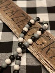 Buffalo Plaid Wood Bead Garland is shown laying across a wood sign.  (Sign is not for sale). The bead colors are white, black and gray with white yarn tassels.