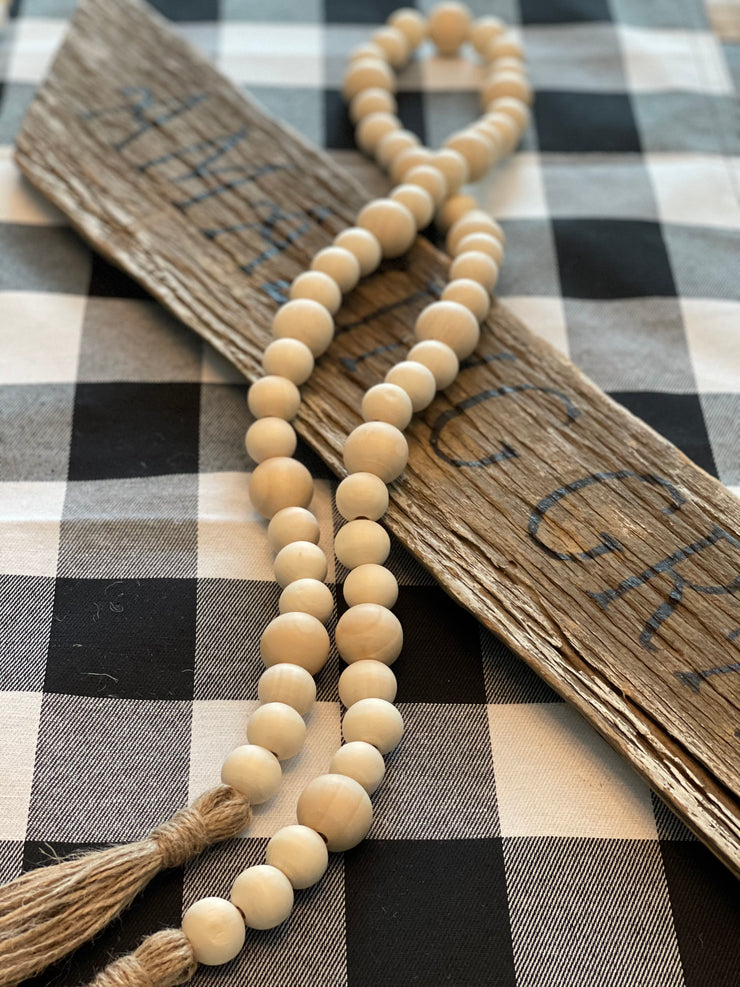Natural Wood Bead Garland is shown draped over a wood sign.  Wood sign is not for sale.