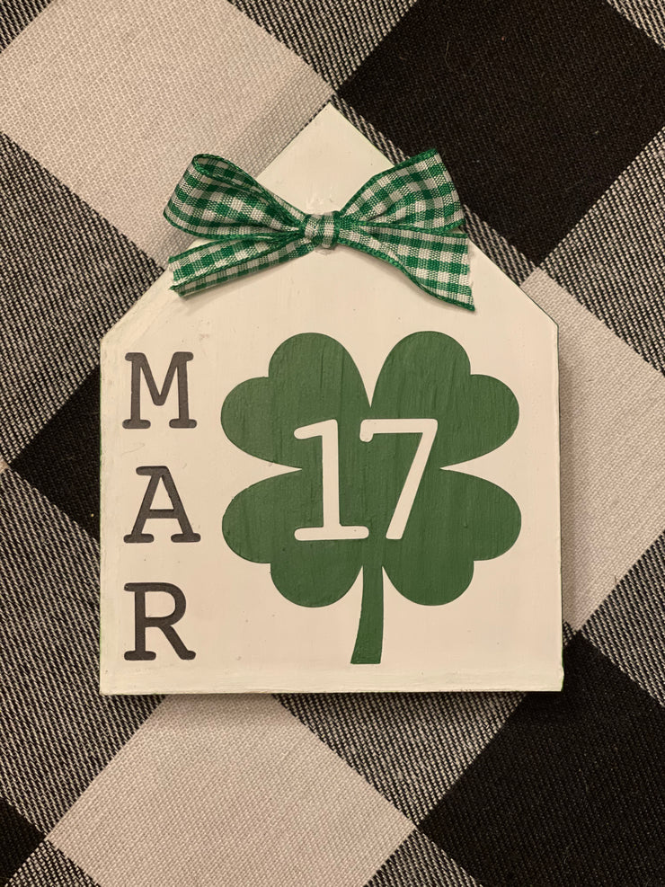 March 17 Mini House Sign is shown sitting on top of a buffalo plaid table runner.