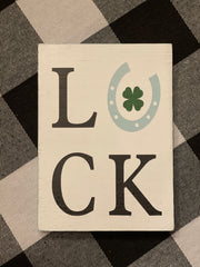 Luck Mini Block Sign is shown displayed on top of a buffalo plaid cloth.