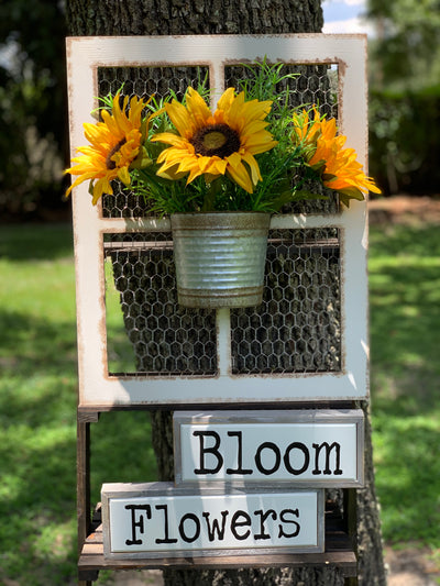 Chicken Wire Wood Window Frame with Galvanized Metal Bucket shows an image with sunflowers added inside the bucket and wood signs that say Bloom and Flowers.  Wood signs and flowers are not sold with this item.