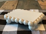 Mini Rectangle Wood Beaded Tiered Tray Riser is shown sitting on a table.
