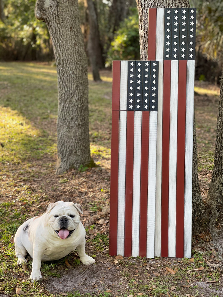 This image shows the two different sizes of the American Flag Porch Sign.  There is a 5 Foot and 4 Foot tall sign.  These are stained, and distressed pine boards with red and white stripes, and blue undertone where 32 3D wood stars are adhered.  Each sign sold separately.  Maggi the English bulldog is also our mascot, and is posing next to the porch leaners.