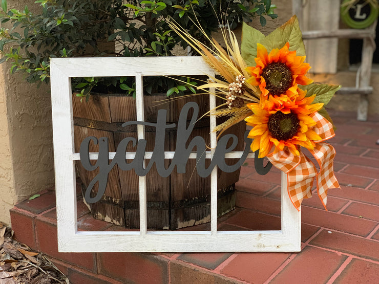"White Distressed Window Frame with ""Gather"" Script is shown sitting on a front porch setting."