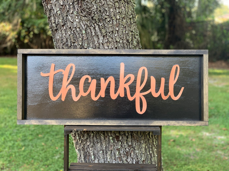 Metallic Thankful Sign shows an image of the sign sitting on a ladder outside.