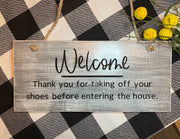 Engraved Welcome Sign / Take Off Your Shoes Door Hanger is shown displayed on a table scape with floral embellishments.  This is the white distressed sign with black lettering.