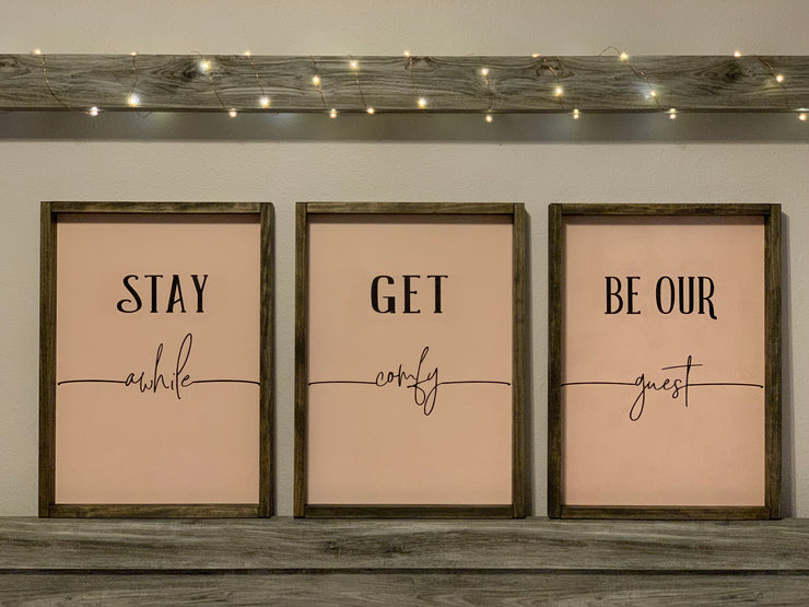 Stay awhile, get comfy, and be our guest signs are shown sitting on a bed mantle side by side.