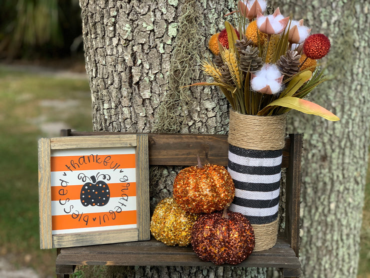 Orange and White Stripe Thankful, Grateful, Blessed (Pumpkin) shows a picture of the sign sitting outside with the black and white stripe burlap vase and pumpkin and floral embellishments.  Items are each sold separately. Pumpkins not eligible for purchase.