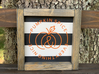 Black and White Stripe Pumpkin Spice and Everything Nice Small Wood Sign shows an image of the sign sitting on a ladder outside.
