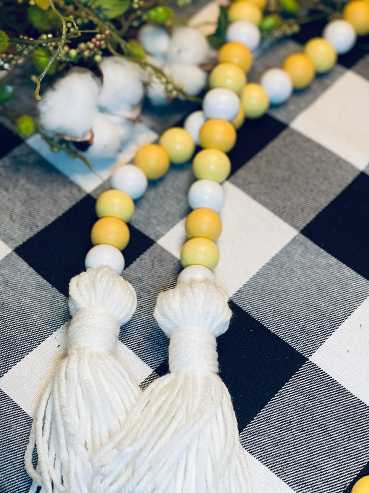 Lemon Wood Bead Garland is beautifully displayed on a table with greenery and cotton embellishments.
