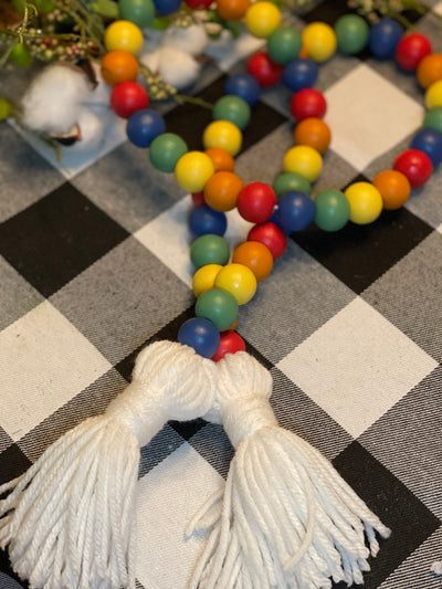 Primary Colored Wood Bead Garland is shown displayed on a table with floral and cotton embellishments.  The colors shown are red, orange, yellow, green and blue with white yarn tassels.