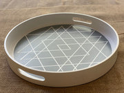 Round Boho White and Gray Tray is shown sitting on a table viewing the angles of the handles.