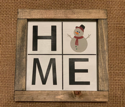 Home Small Sign With Snowman shows an image of the sign sitting on a table.
