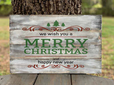 We Wish You A Merry Christmas And Happy New Year Pallet Sign is displayed in an outdoor setting.