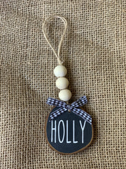 Holly Wooden Beaded Ornament displays the black ornament with white writing and a buffalo check plaid bow sitting on a table.  Each ornament sold separately.