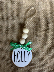 Holly Wooden Beaded Ornament is shown in the white background with black lettering and a green bow.  Each ornament sold separately.