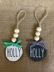 Holly Wooden Beaded Ornament, displays an image of the white and black holly ornaments sitting side by side on a table.  Each ornament sold separately.