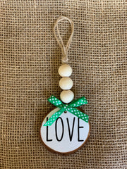 Love Wooden Beaded Ornament displays an image of the white ornament sitting on a table.  Each ornament is sold separately.