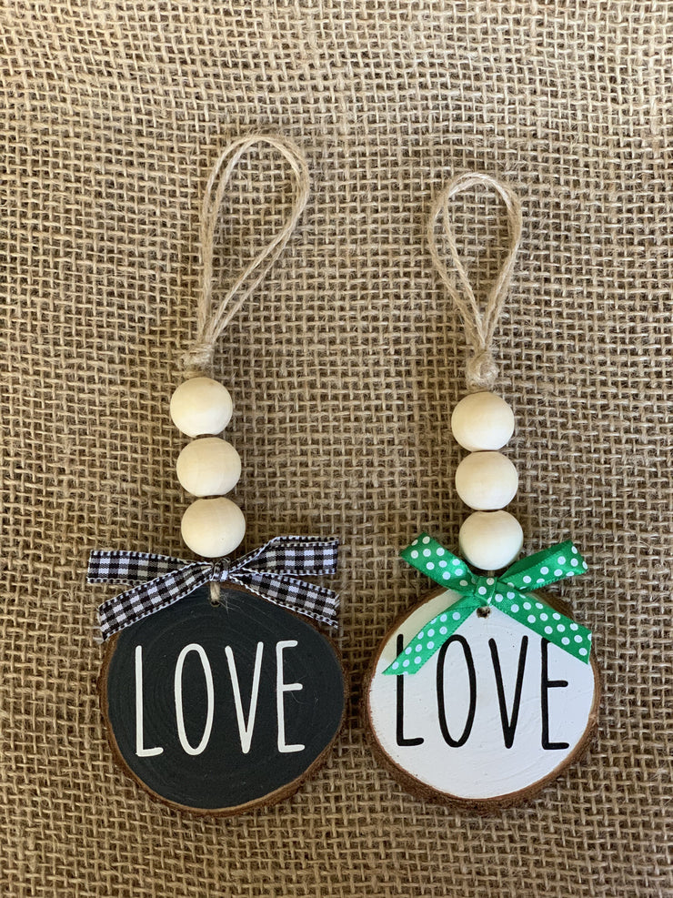 Love Wooden Beaded Ornament displays both the black and white ornaments sitting on a table.  Each ornament is sold separately.
