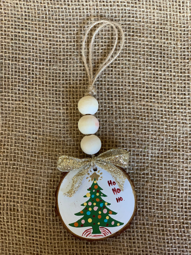 Christmas Tree Wooden Beaded Ornament displays an image of the white painted background with a green painted Christmas tree that says ho ho ho.